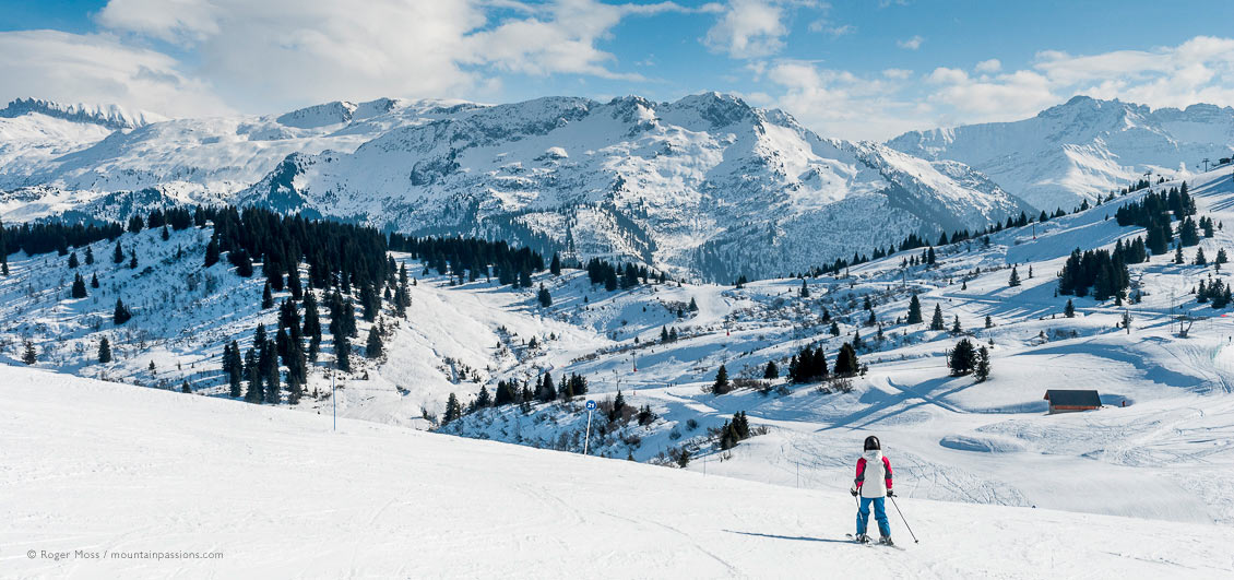 Wide view of young skier amid big-mountain scenery above Les Saisies, French Alps