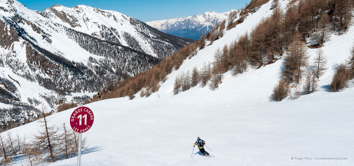 Lone skier on wide tree-lined piste in Les Orres