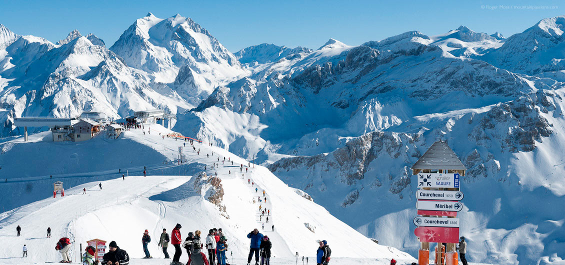 Wide overview of skiers on ridge with ski lifts and mountain background, Meribel