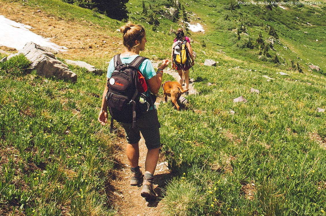 Women walking on a mountain trail with dog. Photo Holly Mandarich