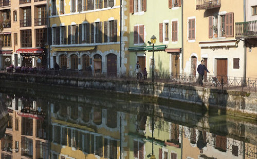 The vibrant pastel colours of the Italianate façades reflected in the calm waters of the canal, Annecy