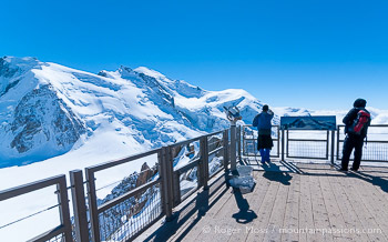 Wide view of visitors on Aiguille du Midi observation deck above Chamonix with Mont-Blanc