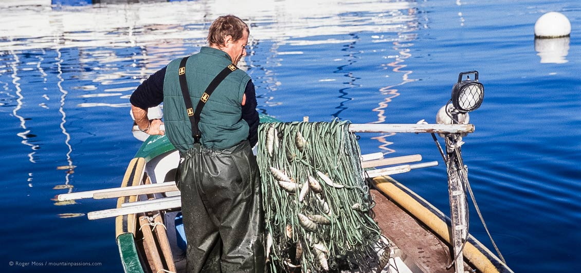 Lac Leman fisherman with his catch at Thonon-les-Bains, French Alps.