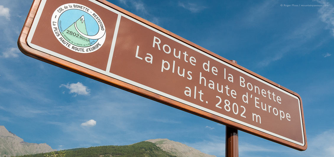 Low view of Route de la Bonette road sign with mountains