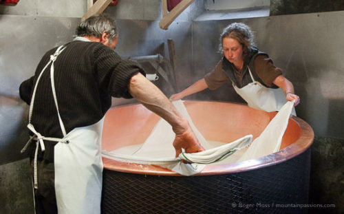 Jean-Pierre Blanc and assistant using muslin cloth to remove cheese from copper vessel while making Beaufort cheese.