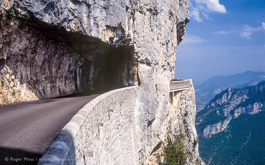 View of high mountain road with rock tunnel and sheer drop