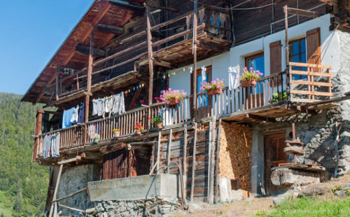 View past firewood stacked on front of grenier to traditional mountain chalet in the Beaufortain, French Alps.