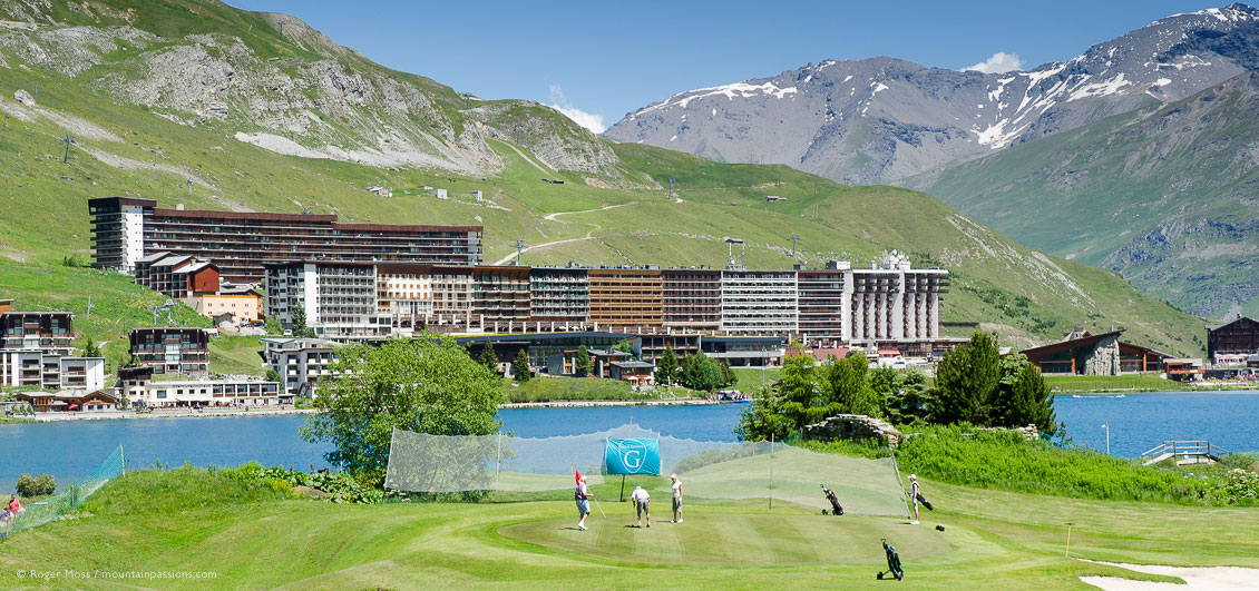 Wide view of Tignes le Lac village beyond lakeside golf course