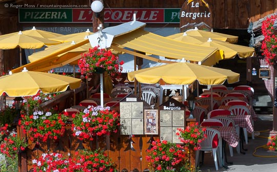 View of pizzeria terrace with parasols and summer flowers