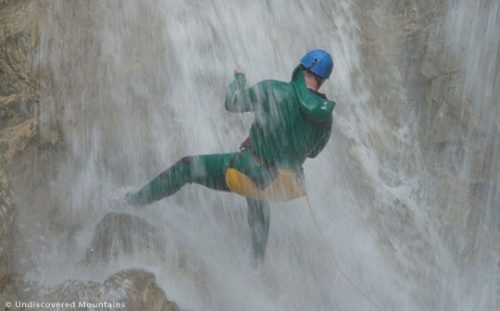 Abseiling under a waterfall, canyoning in the southern French Alps.