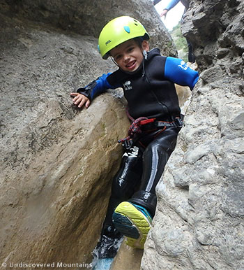 Small boy canyoning wearing all essential equipment.