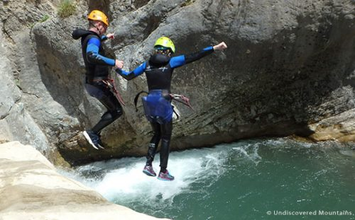 Canyoning couple jumping into pool, southern French Alps.