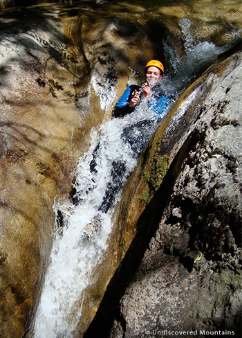 Sliding down a natural water toboggan while canyoning in the southern French Alps.