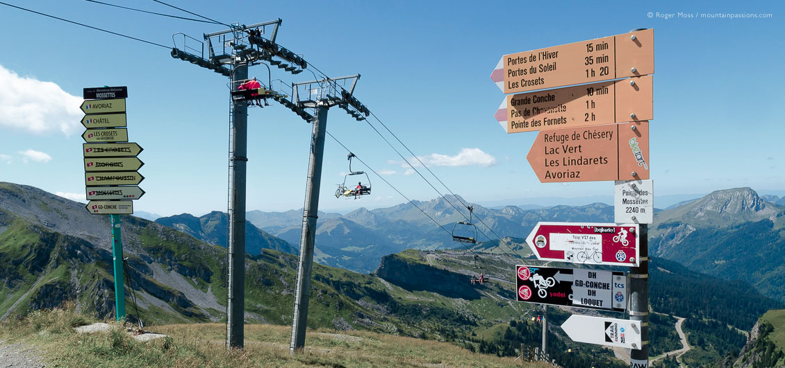 Mountain bikers on chairlift, with trail and footpath signage