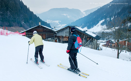 Skiers passing mountain chalets at Areches Beaufort, French Alps.