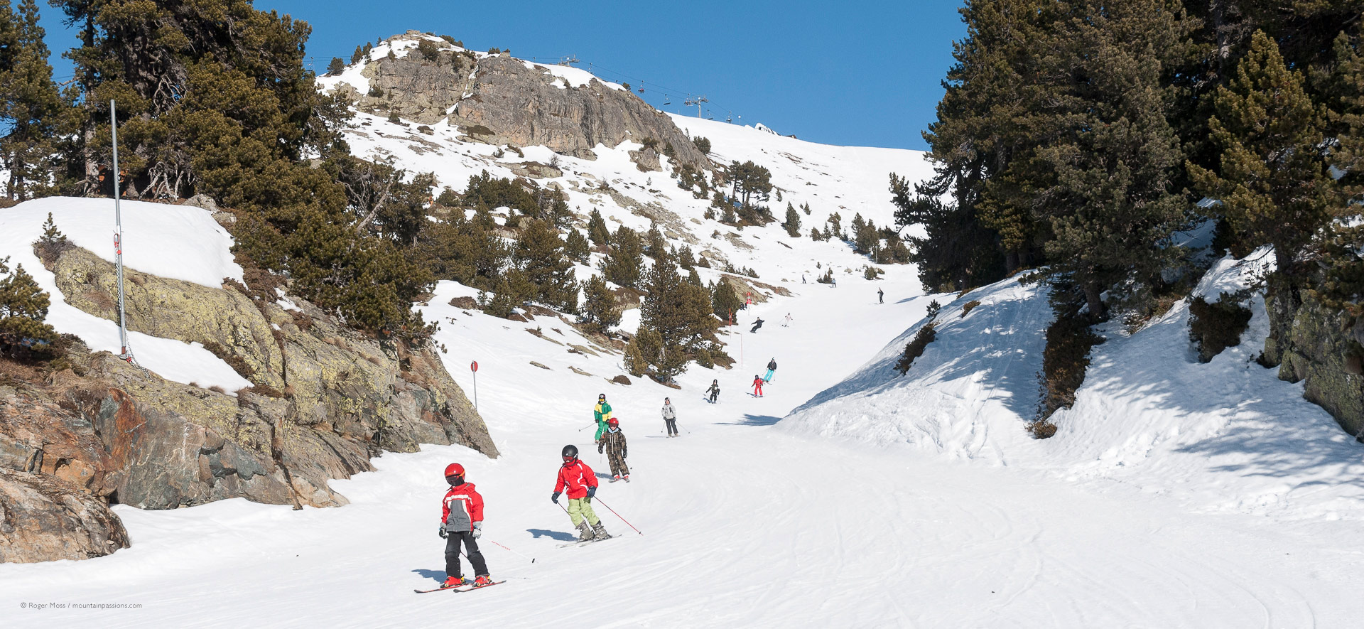 Group of children skiing in bright sunshine at Chamrousse.