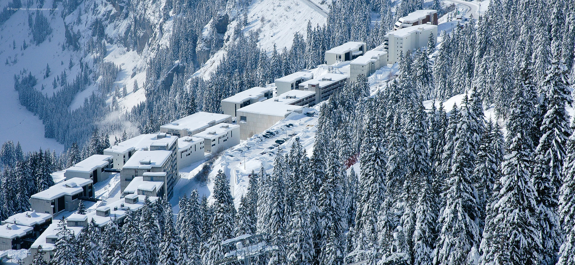 Bird's-eye view of snow-covered apartment blocks an pine forests at Flaine-la-Foret, French Alps.