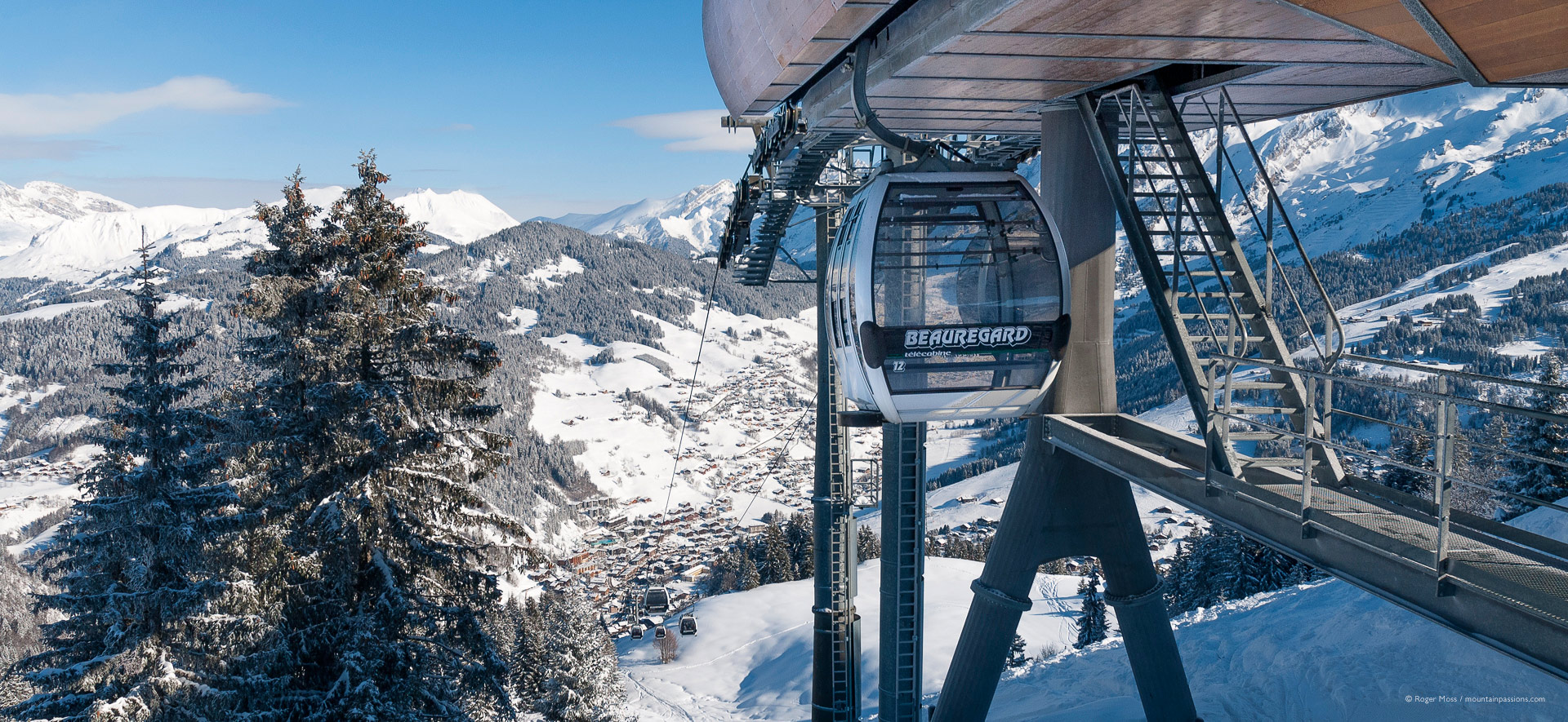 View of approaching cabin of gondola lift above La Clusaz, with village below and mountain backdrop.