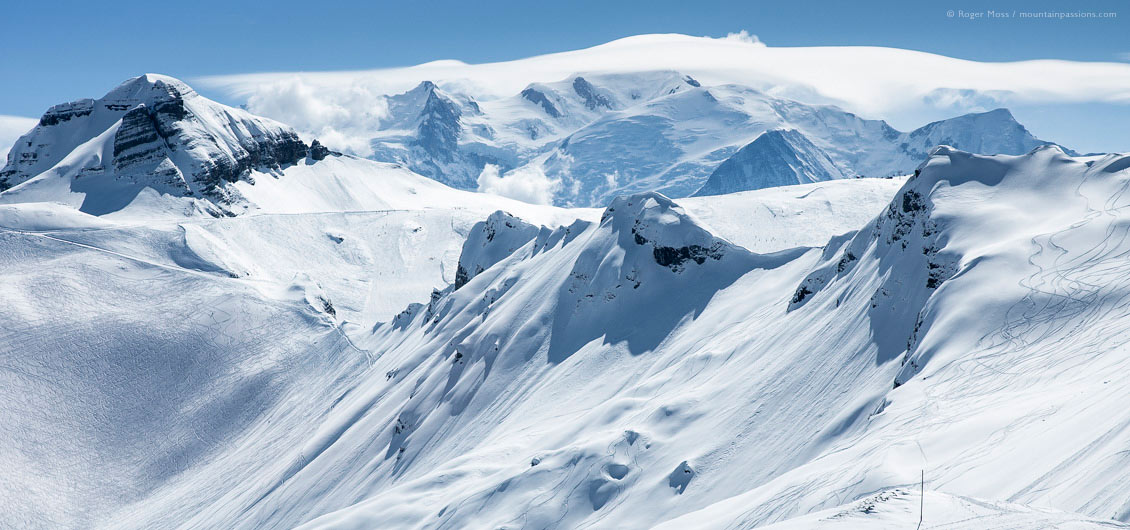 Wide view of snow-covered mountains with ski pistes