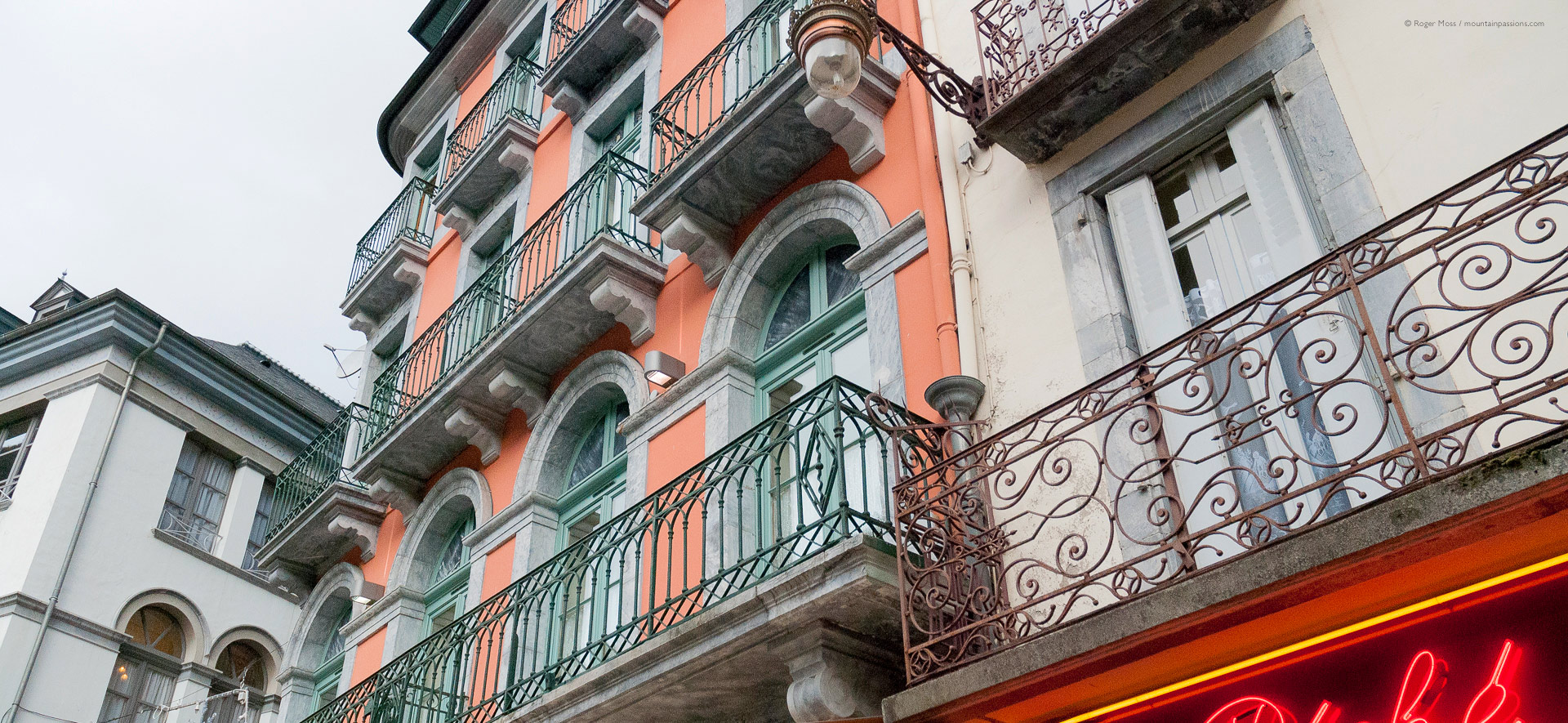 Low view of ornate facades with wrought iron balconies at Cauterets.