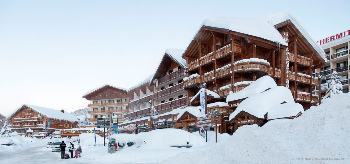 Family beside snow-covered hotels in ski village