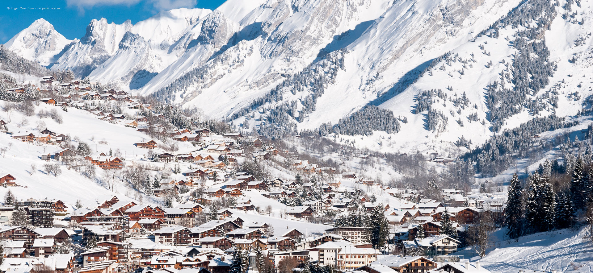 Wide view of La Clusaz rooftops against a backdrop of the snow-covered Aravis mountains