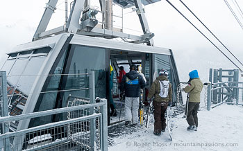 Skiers boarding Vanoise Express cable car, La Plagne, French Alps.