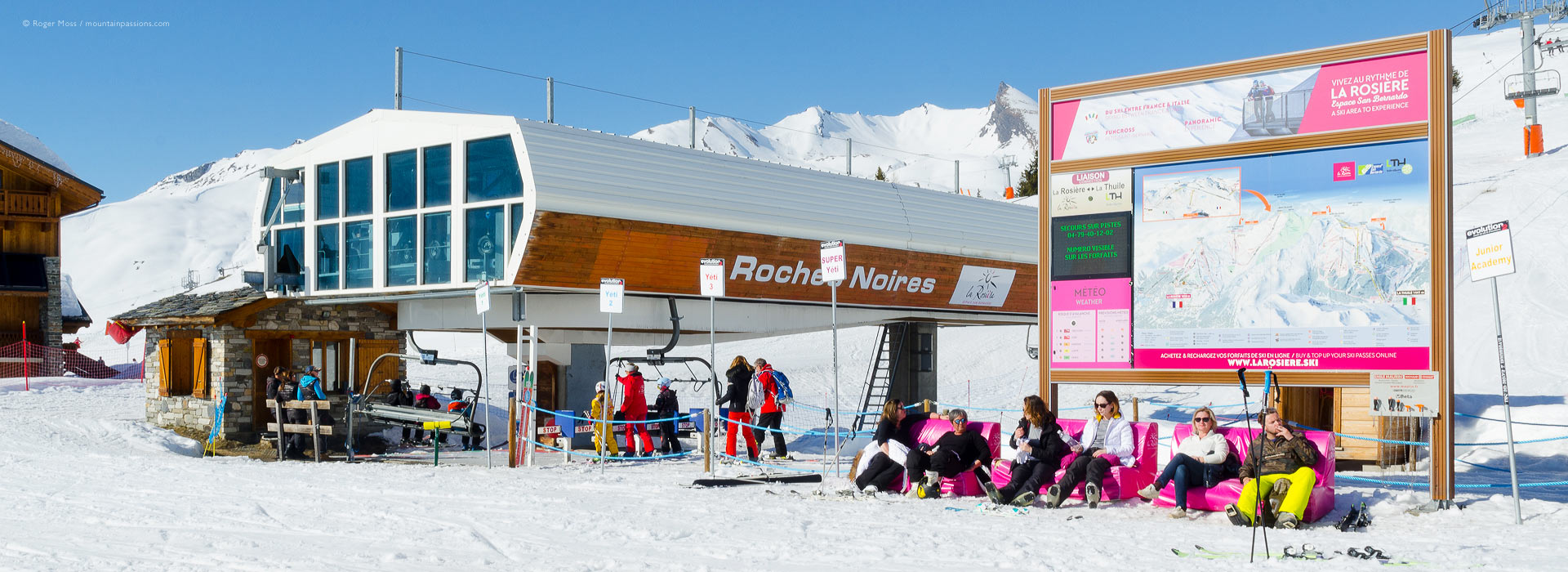 Skiers relaxing around high-speed chair lift at La Rosiere, French Alps