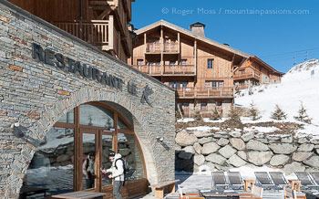 Skier entering mountain hotel restaurant with chalets at Les Menuires.