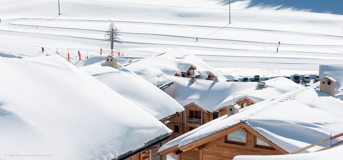 View across snow-covered rooftops to skiers on pistes