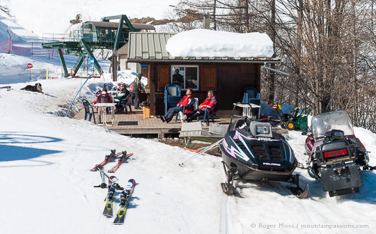 Small mountain bar with skiers and snowmobiles