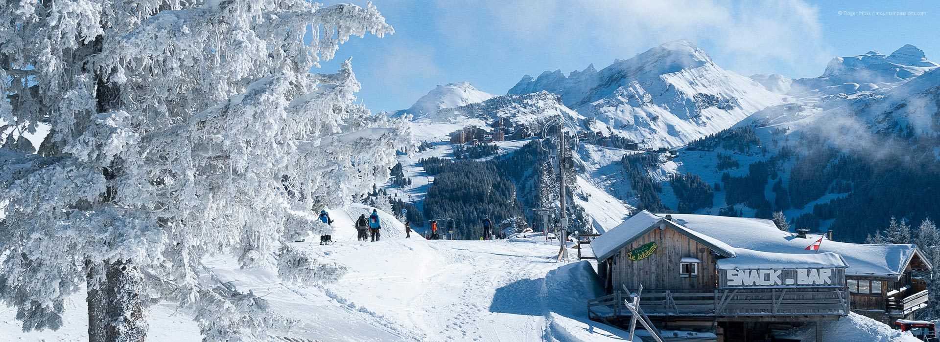 Wide view of skiers amid snowy landscapes.