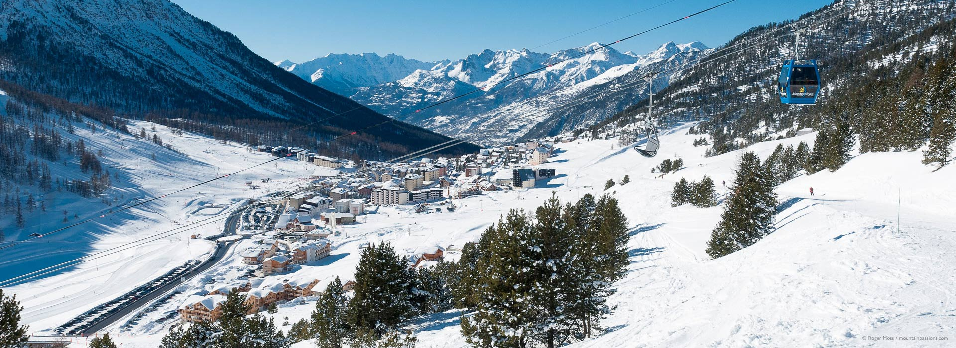 Wide view from chairlift of ski village, valley and mountains at Montgenevre.