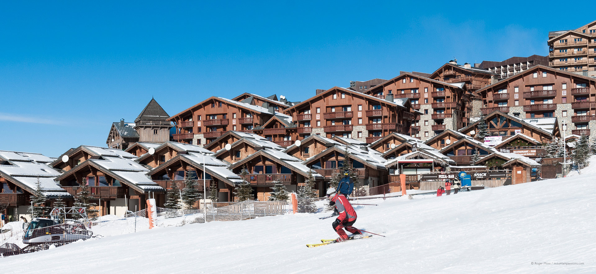 Skier passing recent chalet-style village development at Les Menuires.