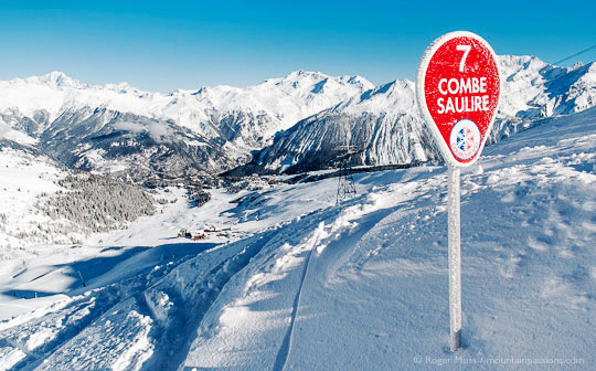 View past piste sign to snow-covered valley, ski village and mountains