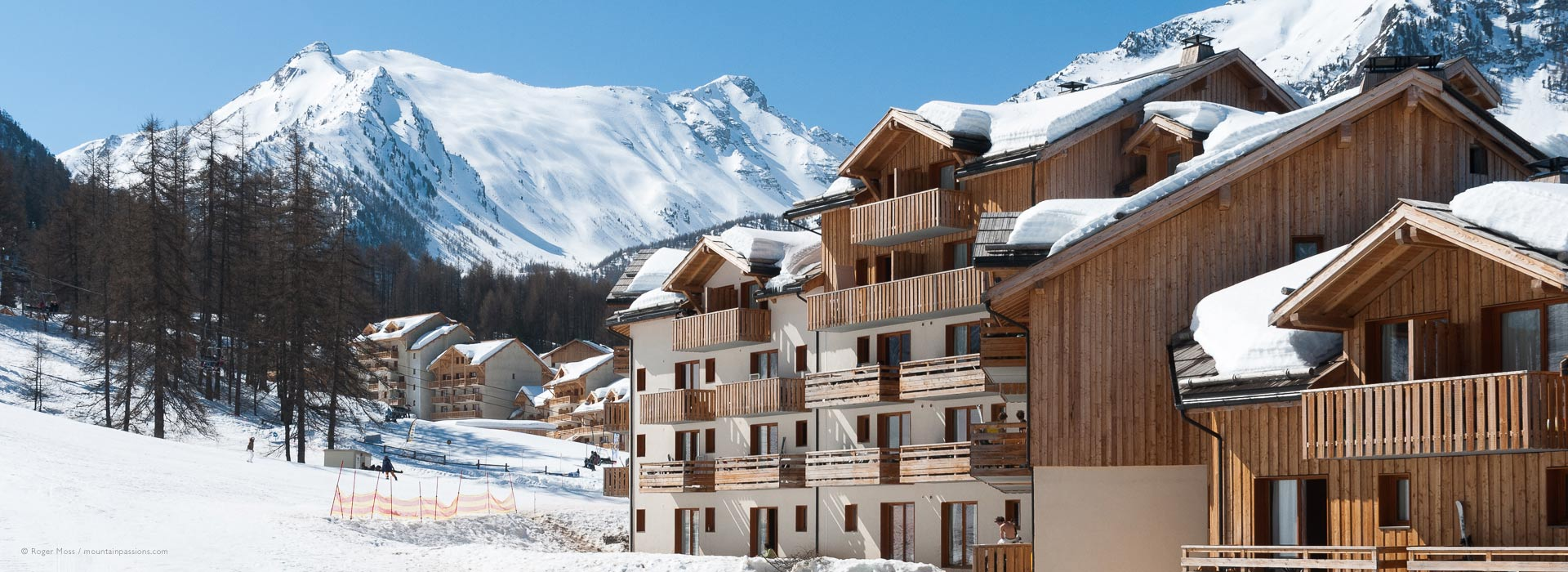 View of ski apartments with snow-covered roofs and mountain background at Les Orres