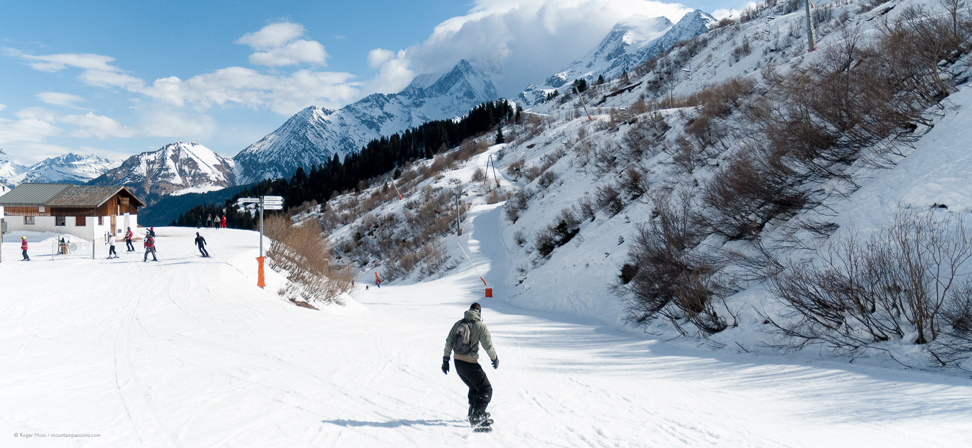 Snowboarder and skiers at junction of pistes with mountain background.
