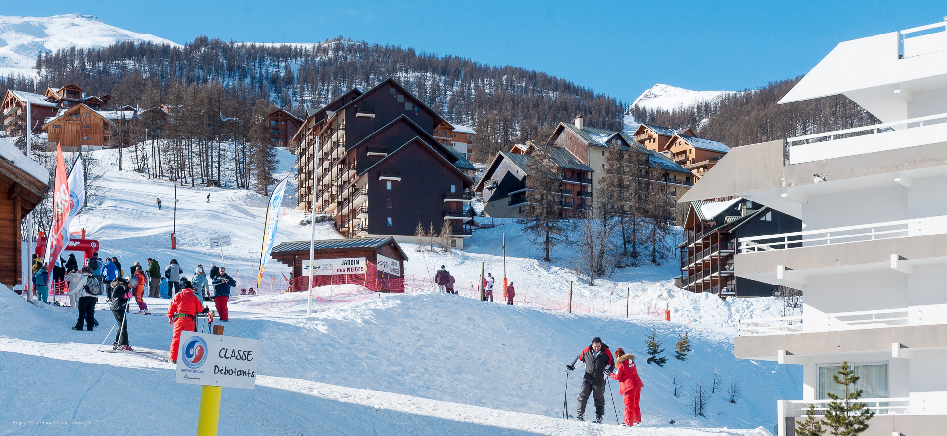 Novice skiers meeting at ski school area, with slopeside apartments in background