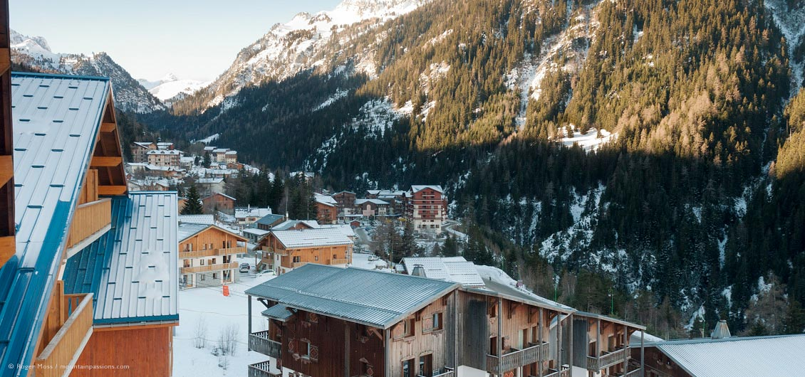 Overview of chalet-style ski village, valley and wooded mountainside
