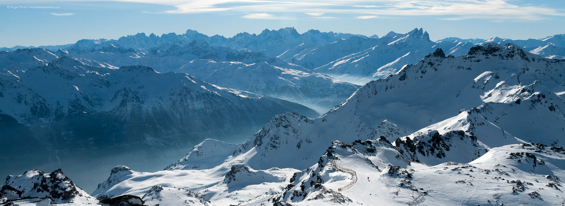 Vast mountain landscape with distant skier descending from Val Thorens to Orelle.