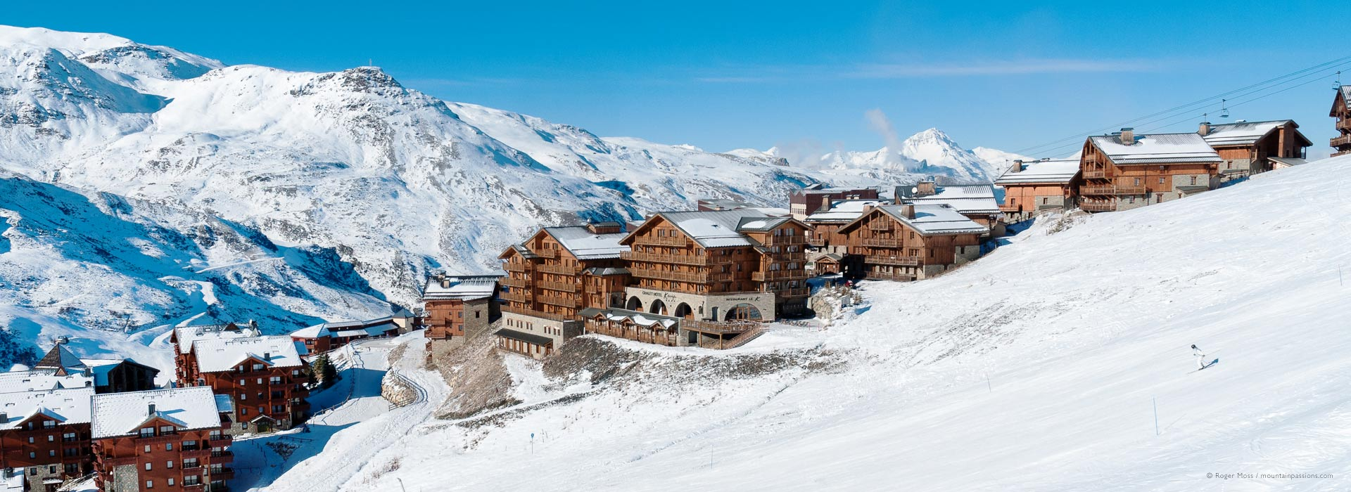 View of chalets at Les Menuires ski resort with snow-covered mountainside, 3 Valleys, French Alps.
