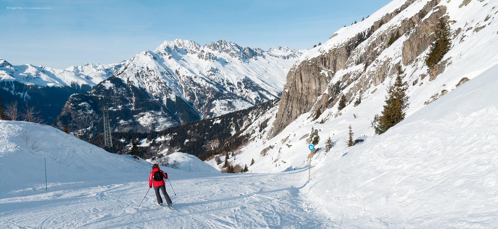 Skier descending piste between rocky outcrops