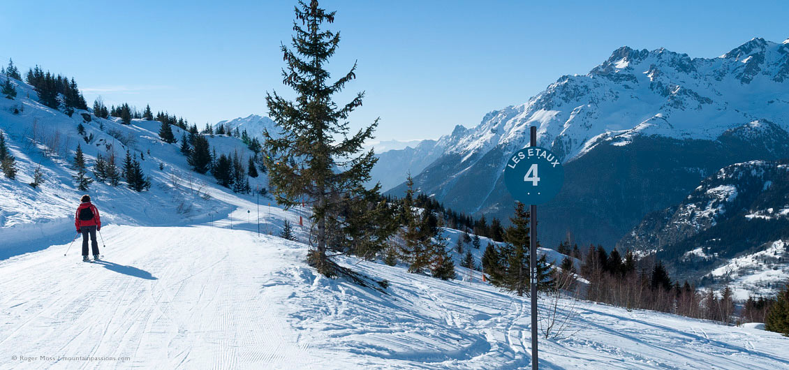 Wide view of lone skier on piste with valley views