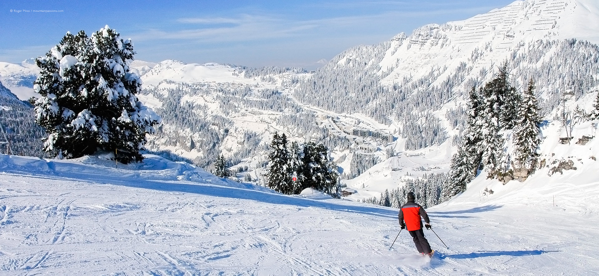 Rear view of skier on return piste with Flaine la Foret some distance ahead.