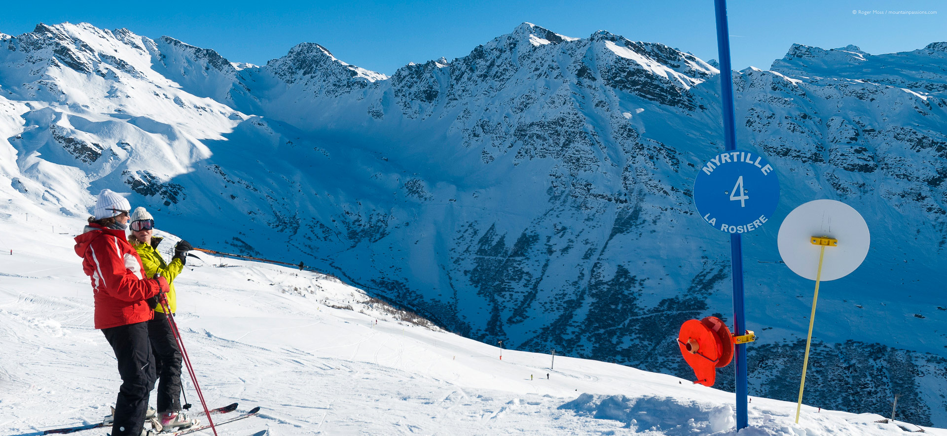 Skier above ski chalets with mountains in background at La Rosiere.