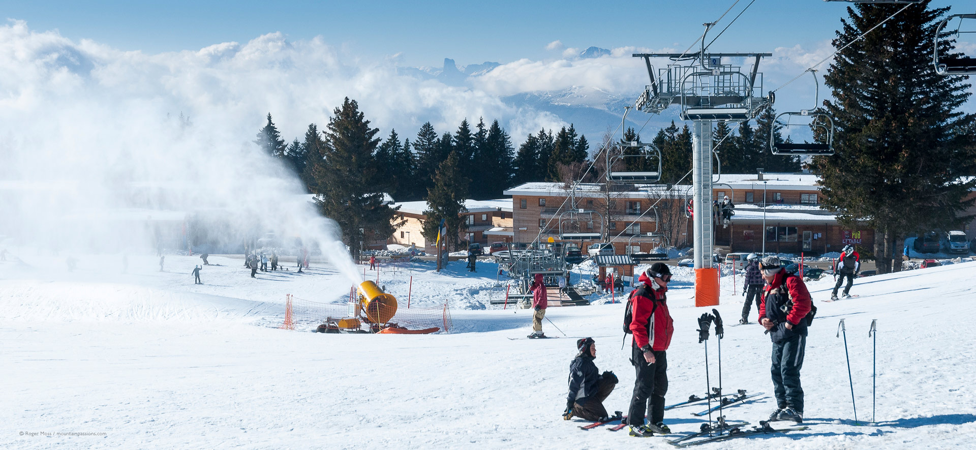 Skiers with snow-making above the ski village of Chamrousse.