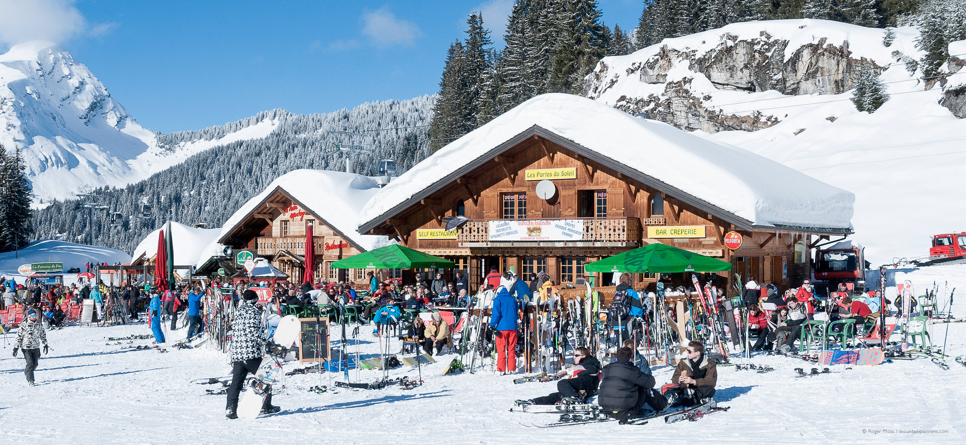 Large groups of skiers outside mountain restaurants