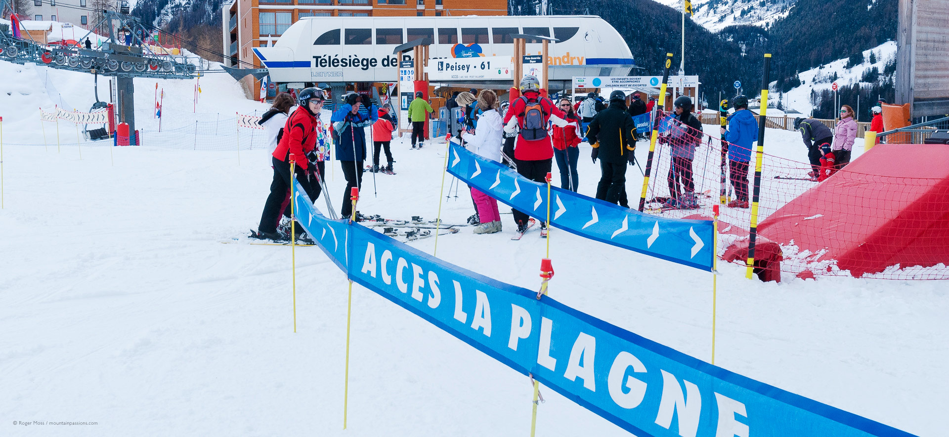 Skiers beside signs to liason with La Plagne, with ski-lifts in background.