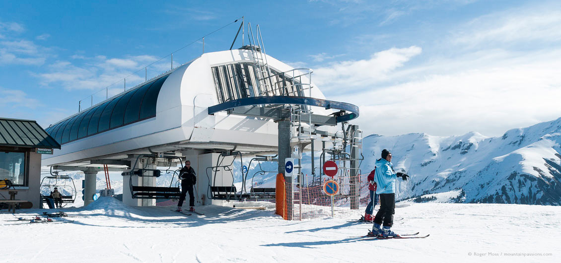 Skiers leaving high speed chairlift with snowy mountain background