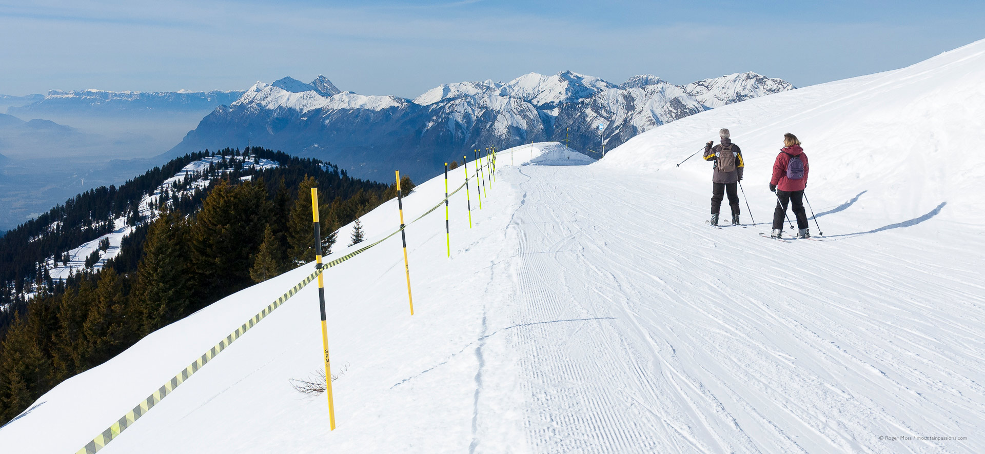 Close view of two skiers on piste, showing Espace Diamant ski area, above Crest Voland.